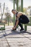 Eine junge lächelnde Frau, Spitzee binden, draußen Turnhalle im Park, lizenzfreie stockfotos