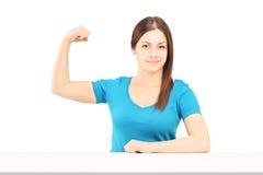 Eine junge lächelnde Frau, die ihren Bizepsmuskel zeigt Stockbilder