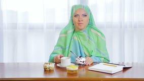 Eine junge moslemische Frau in einem hellen Schal in einem Café isst Kuchen und trinkt Tee stock footage