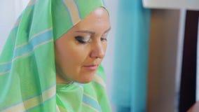 Eine junge moslemische Frau in einem hellen Schal in einem Café isst Kuchen und trinkt Tee stock video