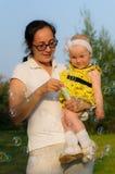 Eine junge Mutter, die ein Baby hält und Blasen durchbrennt stockfoto