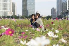 Eine junge Mutter hält den Jungen glücklich im Stadtpark Stockfoto