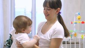 Eine junge Mutter hält ein geliebtes Kind in ihren Armen, und sie lachen, wenn sie spielen stock video footage