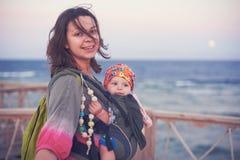 Eine junge Mutter ist auf dem Strand mit ihrem Baby in einem Riemen lizenzfreie stockfotos