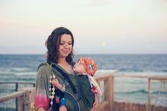 Eine junge Mutter ist auf dem Strand mit ihrem Baby in einem Riemen lizenzfreies stockfoto