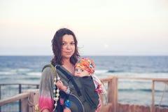 Eine junge Mutter ist auf dem Strand mit ihrem Baby in einem Riemen stockfoto