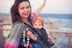 Eine junge Mutter ist auf dem Strand mit ihrem Baby in einem Riemen stockbild