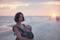 Eine junge Mutter ist auf dem Strand mit ihrem Baby in einem Riemen stockfotografie