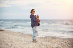 Eine junge Mutter ist auf dem Strand mit ihrem Baby in einem Riemen lizenzfreie stockfotografie