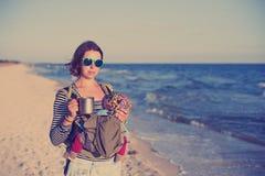 Eine junge Mutter ist auf dem Strand mit ihrem Baby in einem Riemen stockfotos