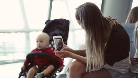 Eine junge Mutter macht ein Foto ihres kleinen Sohns in einem Pram an einem Handy stock video footage