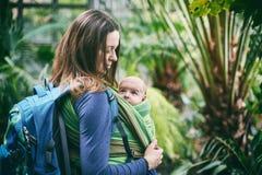 Eine junge Mutter mit einem Baby in einem Riemen geht in den Dschungel lizenzfreie stockfotos