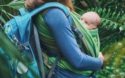 Eine junge Mutter mit einem Baby in einem Riemen geht in den Dschungel stockfotos