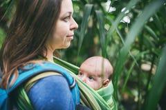 Eine junge Mutter mit einem Baby in einem Riemen geht in den Dschungel lizenzfreie stockbilder