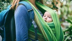 Eine junge Mutter mit einem Baby in einem Riemen geht in den Dschungel lizenzfreies stockbild