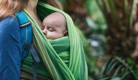 Eine junge Mutter mit einem Baby in einem Riemen geht in den Dschungel stockfoto