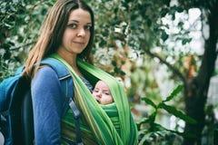 Eine junge Mutter mit einem Baby in einem Riemen geht in den Dschungel lizenzfreie stockfotografie