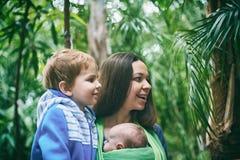 Eine junge Mutter mit einem Baby in einem Riemen und in einem kleinen Jungen geht in den Dschungel lizenzfreie stockfotos