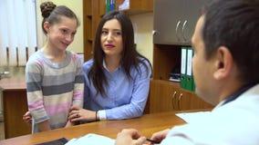 Eine junge Mutter mit einem Kind zum Doktor Der Doktor gibt dem Mädchen ein therapeutisches Mittel stock video