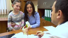 Eine junge Mutter mit einem Kind zum Doktor Der Doktor gibt dem Mädchen ein therapeutisches Mittel stock footage