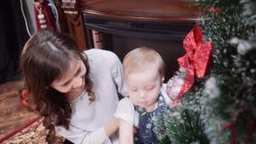 Eine junge Mutter mit einem kleinen Sohn in einem Raum nahe dem Kamin einen Weihnachtsbaum oben kleidend stock footage
