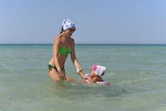 Eine junge Mutter mit einem kleinen Tochterschwimmen im Meer stockfoto