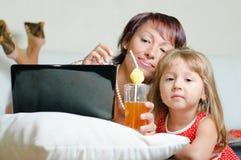 Eine junge Mutter mit einem Notizbuch und einer Tochter Lizenzfreies Stockfoto