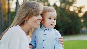 Eine junge Mutter mit ihrem Babysohn geht in den Park Mutter zeigt dem Kind interessantes etwas stock video