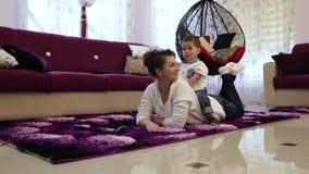 Eine junge Mutter mit ihrem kleinen Sohn, der auf dem Boden im Wohnzimmer und Uhr Fernsehen liegt stock video footage