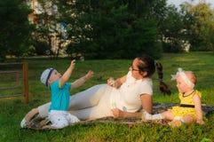 Eine junge Mutter mit ihrem Sohn und Tochter liegen auf dem Gras und sind mit Seifenblasen glücklich stockbild