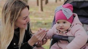 Eine junge Mutter mit ihrer Tochter in einem Kinderwagen steht in Verbindung stock video
