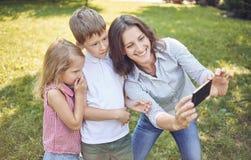 Eine junge Mutter mit Kindern geht in den Park und tut selfie mit ihnen Stockfotos