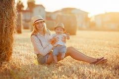 Eine junge Mutter mit kleinem Baby in der Kappe, die auf einem backgro sitzt Lizenzfreie Stockbilder