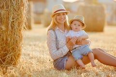 Eine junge Mutter mit kleinem Baby in der Kappe, die auf einem backgro sitzt Lizenzfreie Stockfotos
