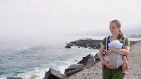 Eine junge Mutter reist auf den Strand mit ihrem Baby in einem Riemen stock video footage