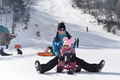 Eine junge Mutter reist in die Berge mit ihrer wenigen Tochter auf einem sonnigen Winter lizenzfreie stockfotos
