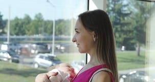 Eine junge Mutter schaukelt einen kleinen Sohn auf einer Hand vor einem Fenster stock video