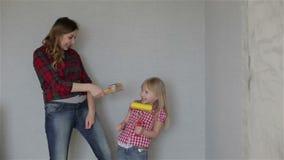 Eine junge Mutter und eine Tochter, die mit einem Pinsel singen stock video