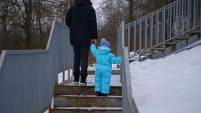 Eine junge Mutter und ihr kleiner Junge gehen herauf die Treppe stock footage