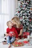 Eine junge Mutter und ihr Sohn sitzen nahe einem schönen  Ð Weihnachtsbaum Ð ÐºÑ€Ð°Ñ ½ Ð ¾ Ñ  Ñ  Ð ² Ð¸Ñ 'Ð?Ñ€Ð? Stockfotografie