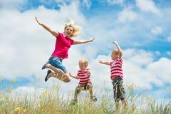 Eine junge Mutter und zwei kleine Söhne, die den spielenden und springenden Spaß haben stockfoto