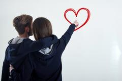 Eine junge Paarstellung, welche zurück die weiße Wand betrachtet, stellt zum Herzen dar lizenzfreie stockbilder