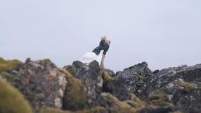 Eine junge Paarumarmung unter den Felsen stock video footage