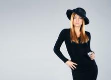Eine junge Redheadfrau in einem schwarzen Retro- Kleid Lizenzfreie Stockfotografie