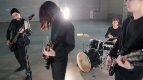 Eine junge Rockgruppe, die eine Wiederholung in einer Garage hat Mitglieder einer Gruppe, die schwarze Kleidung trägt lizenzfreies stockfoto
