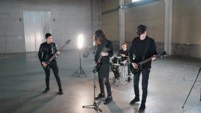 Eine junge Rockgruppe, die eine Wiederholung in einer Garage hat stockfoto