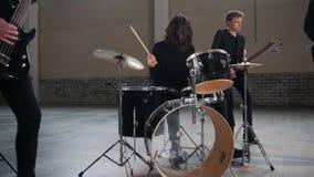 Eine junge Rockgruppe, die eine Wiederholung hat Ein Mann mit dem langen Haar, das Trommeln spielt stock video footage