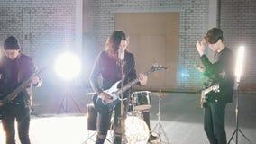 Eine junge Rockgruppe, die zu einer Wiederholung in einem großen Raum fertig wird stock video footage