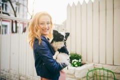 Eine junge rothaarige kaukasische Frau hält einen kleinen lustigen Hund in den Armen von zwei Farben von Schwarzweiss-Chihuahua U lizenzfreie stockfotografie