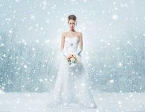 Eine junge Rothaarigebraut in einem weißen Kleid auf dem Schnee Lizenzfreie Stockbilder